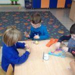 troje dzieci siedzących przy stole, ozdabiających ziemniaki.