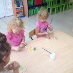 Trzy dziewczynki siedzące przy stoliku i ozdabiające ziemniaki.
