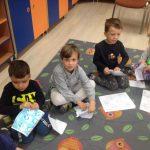 Czworo dzieci siedzących na dywanie i trzymających kartki papieru