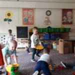 Dzieci bawiące się na dywanie klockami oraz autami