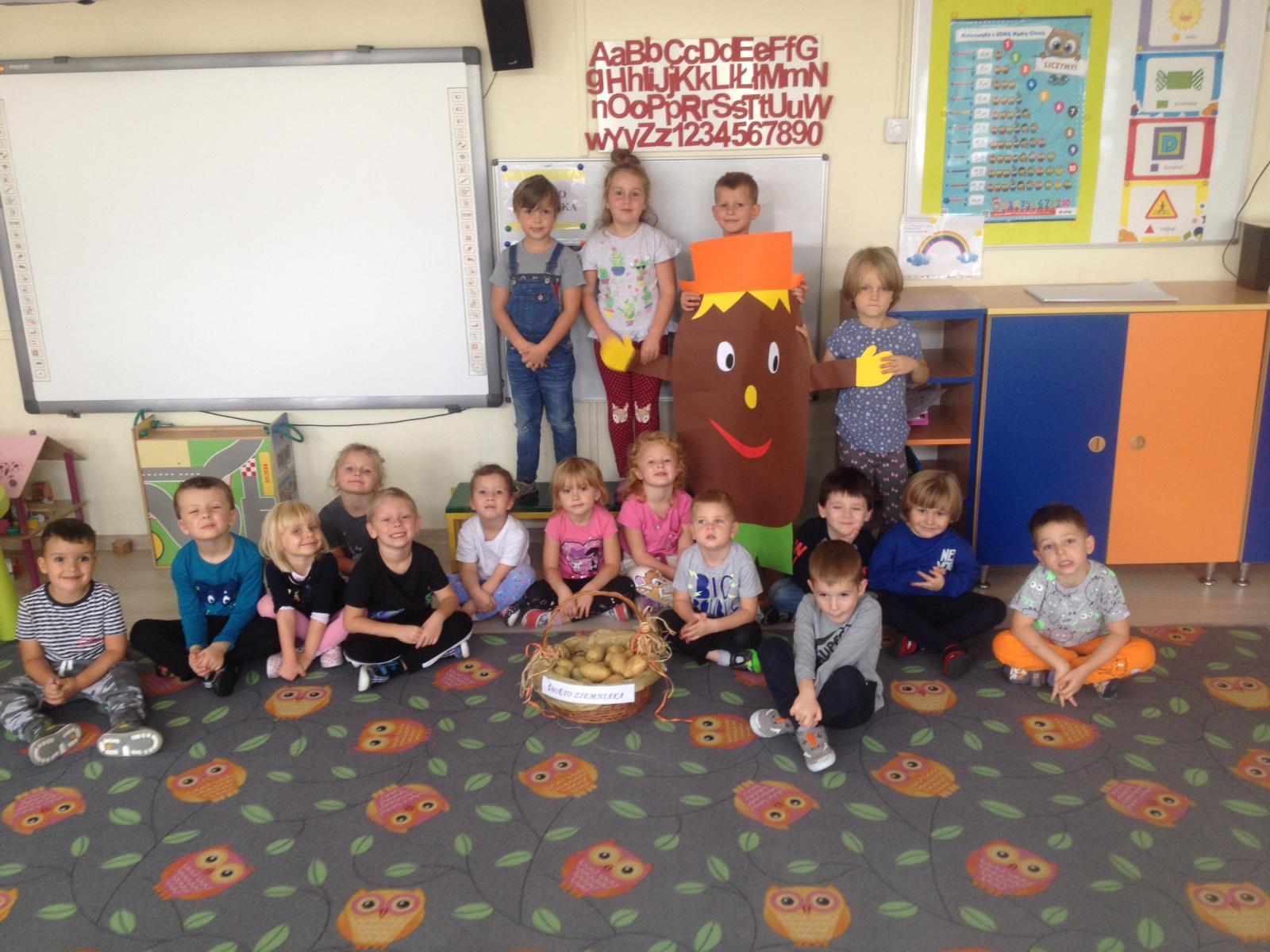 Trzynaścioro dzieci siedzących na dywanie przed którymi stoi koszyk z ziemniakami. Za nimi czworo stojących dzieci.