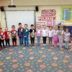 Grupa dzieci stoi na dywanie w półkolu w rękoma wzdłuż tłowia. Każde dziecko ma przypięty biało-czerwony kotylion.