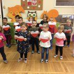 Grupa dzieci stoi w trzech rzędach. Każde dzieci trzyma w rękach papierowe serce biało-czerwone.