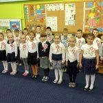 Grupa dzieci stoi ubrana na galow. Każde dziecko ma przypięty biało-czerwony kotylion.