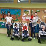 3 dzieci siedzi na swoim wózku. Po środku wózków stoi nauczycielka z dzieckiem na ręku. Po lewej stronie stoi nauczycielka trzymająca chłopca za rękę.. Każde dziecko ma przypięty biało-czerwony kotylion.