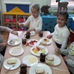 Kilkoro dzieci siedzi na krześle przy stole. Na stole leżą talerze, pokrojone warzywa, chleb z masłem i kubek z herbatą.