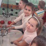 Dwie dziewczynki stoją przy umywalce i myją ręce.