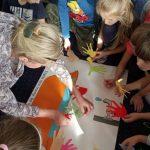 Grupa dzieci i nauczycielka przyklejają wycięte dłonie z papieru na kartkę.