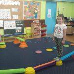 Na dywanie, jest rozstawiona jest kolorowa ścieżka . Jedno dziecko po niej chodzi.