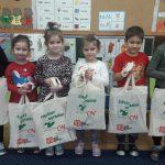 6 dzieci stoi trzymając w rękach materiałowe torby