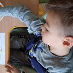 Dziecko siedzi przy stoliku. Na kartce papieru maluje palcami kolorowe kropki.