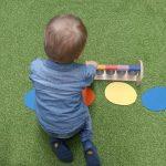 Dziecko siedzi na dywanie . Przed sobą ma kolorowe połkola i dzwonki. Gra na tych dzwonkach .