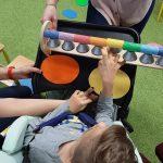 Dziecko siedzi na wózku . Przed sobą ma kolorowe połkola i dzwonki. Gra na tych dzwonkach .