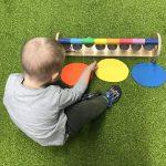 Dziecko siedzi na dywanie . Przed sobą ma kolorowe połkola i dzwonki.