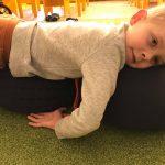 Dziecko leży na wałku wypełnionym łuską gryki.