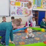 Dzieci siedzą wkoło dywanu, na którym rozstawiona jest kolorowa ścieżka . Dwoje dzieci po niej chodzi.