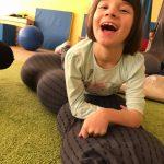 Dziecko leży na wałku wypełnionym łuską gryki podtrzumując się na rękach. Dziewczynka uśmiecha się szeroko.