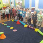 Dzieci stoją wkoło dywanu, na którym rozstawiona jest kolorowa ścieżka.