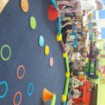 Dzieci siedzą wkoło dywanu, na którym rozstawiona jest kolorowa ścieżka . Jedno dziecko po niej chodzi.