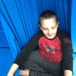 Dziecko siedzi w niebieskim hamaku.