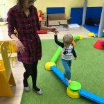 Dziecko chodzi po rozłożonej na dywanie ścieżce, trzymając za rękę nauczycielkę.