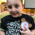 Chłopiec w czarnej bluzce ma zalepiony medal w misiem.