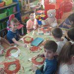 Grupa dzieci siedzi przy stoliku, trzyma w ręce pędzelek i maluje okrągłe papierowe talerzyki.