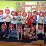 Duża grupa dzieci trzymają przy twarzy okrągłe papierowe talerzyki wycięte po środku i pomalowane na brązowo. Połowa dzieci siedzi na dywanie, a połowa stoi za nimi.