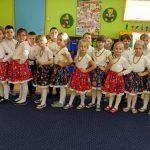 Dzieci stoją w 2 rzędach. Z przodu dziewczynki ubrane w spódniczki w kwiaty, z tyłu chłopcy w białych koszulach