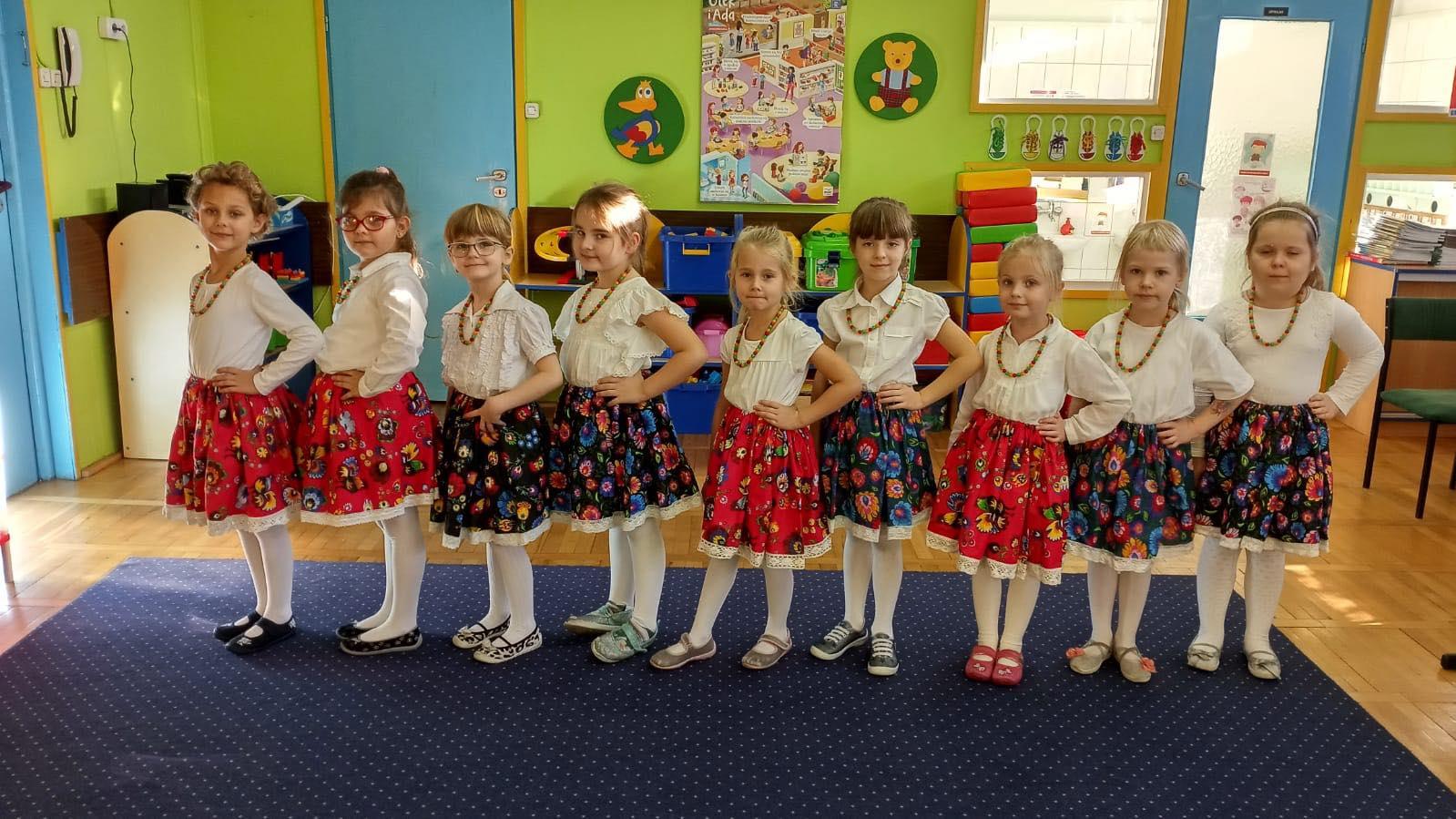 Kilka dziewczynek stoi w rzędzie ubrane w spódniczkę w kwiatki.