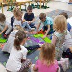 Grupa dzieci bawiących się na dywanie kolorowymi klockami.