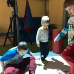 Trzech chłopców bawiących się na dywanie interaktywnym.