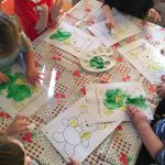 Dzieci siedzący przy stole malujących farbami kolorowanki przedstawiające misie.