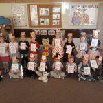 Zdjęcie grupowe dzieci znajdujących się w sali przedszkolnej, mających na głowie opaski z ilustracją misia i pokazujących dyplomy.
