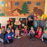 Grupa dzieci siedzących na dywanie i machających rękami. Dzieci mają na głowach założone kolorowe opaski.