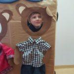 Chłopiec pozujący do zdjęcia w ramce przedstawiającej misia.