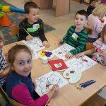 Dzieci siedzące przy stolikach i wykonujących farbami prace plastyczne: misie.