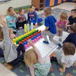 Grupa dzieci siedzących w kole na dywanie. Po środku znajduje się mata z ułożonymi na niej kolorowymi kubkami.