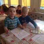 Dzieci siedzące przy stole i malujących farbami obrazki przedstawiające misie.