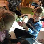 Kilkoro dzieci bawiących się na dywanie interaktywnym. Za nimi siedząca na dywanie nauczycielka.