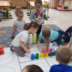 Kilkoro dzieci siedzących na dywanie. W środku znajduje się mata, na której ułożona jest wieża z kolorowych kubków. Dwoje dzieci trzyma w ręku plastikowe kubki. Jeden chłopiec układa z kubków wieżę.