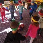 Trzymające się za ręce dzieci tańczące w kółku. W środku koła znajduje się dziecko leżące na dywanie.