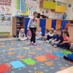 Dziewczynka stąpająca po przyklejonej na dywanie taśmie stopa za stopą. Z tyłu dzieci siedzące na dywanie po turecku.