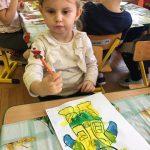 Dziewczynka siedząca przy stoliku i trzymająca kredkę. Przed nią pomalowany farbami obrazek przedstawiający misia. Za nią dzieci siedzące na krzesłach przy stoliku.