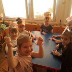 Dzieci siedzący przy stolikach, mający przed sobą batoniki i lizaki.