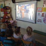 Sześcioro dzieci siedzących na krzesłach i oglądających bajkę wyświetlaną na tablicy multimedialnej.
