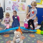 Dwoje dzieci pokonujący tor przeszkód znajdujący się na dywanie. Przed nimi pluszowy miś, za nimi troje dzieci siedzących na dywanie.