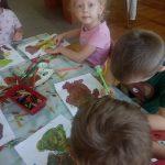 Czworo dzieci siedzących przy stoliku malujących farbami obrazki przedstawiające misie.