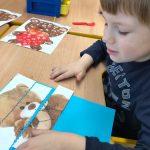 Chłopiec siedzący przy stoliku i układający puzzle przedstawiające obrazek misia.