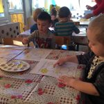 Dzieci siedzące przy stolikach i malujących farbami obrazki przedstawiające misie.